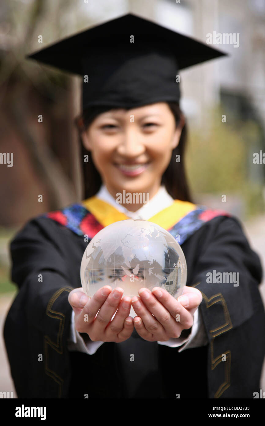 Chinese girl in graduation gown holding crystal ball,China Stock ...