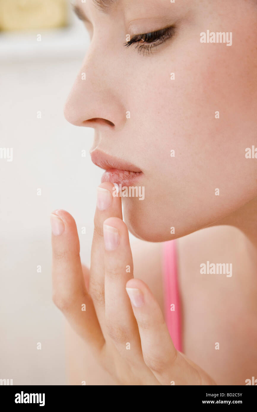 woman applying ointment for cold sore - Stock Image