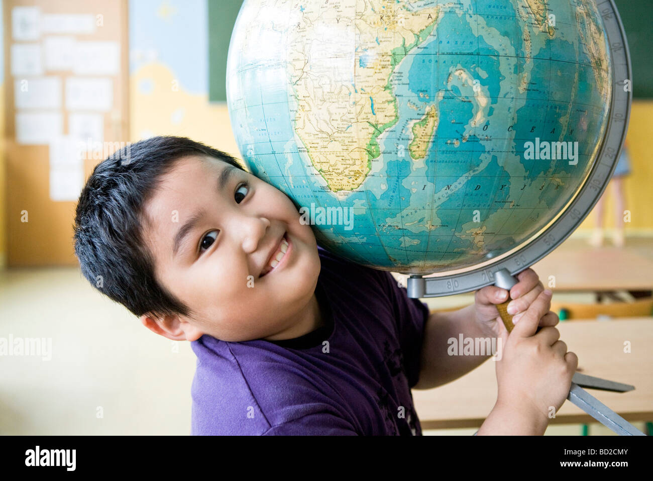 boy with globe in class - Stock Image