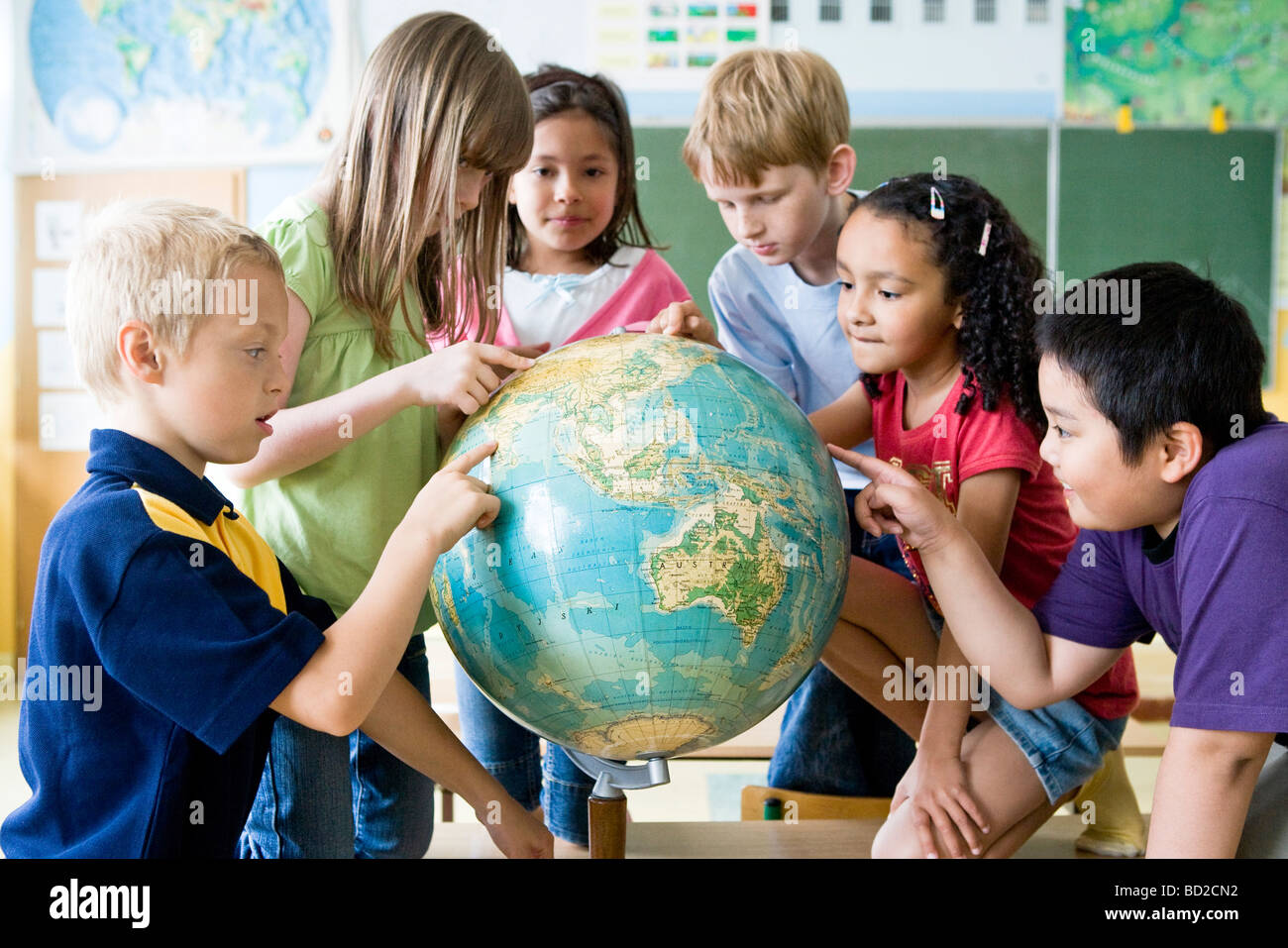 children looking at globe in class - Stock Image