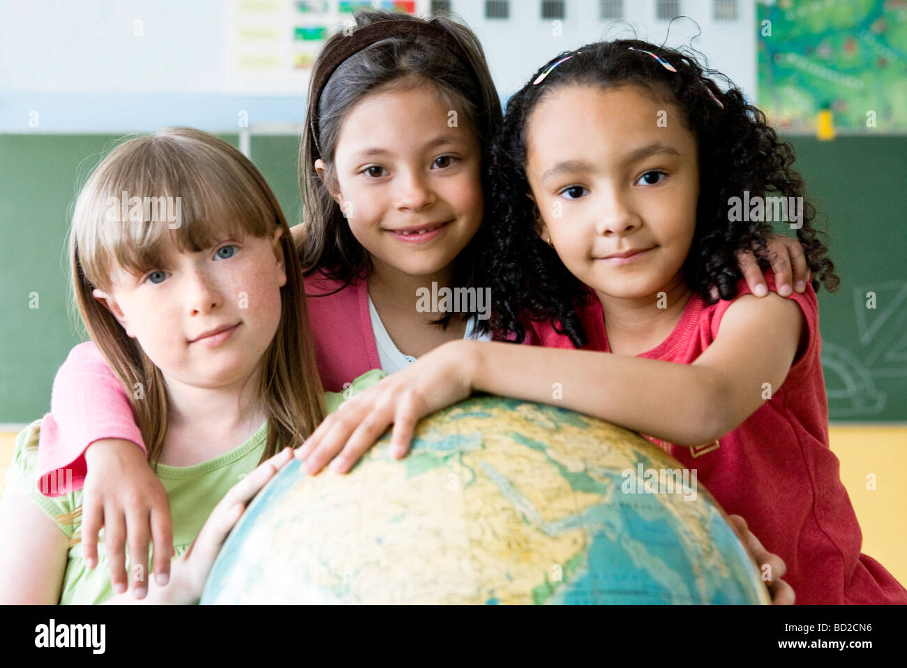 girls hugging globe in class - Stock Image