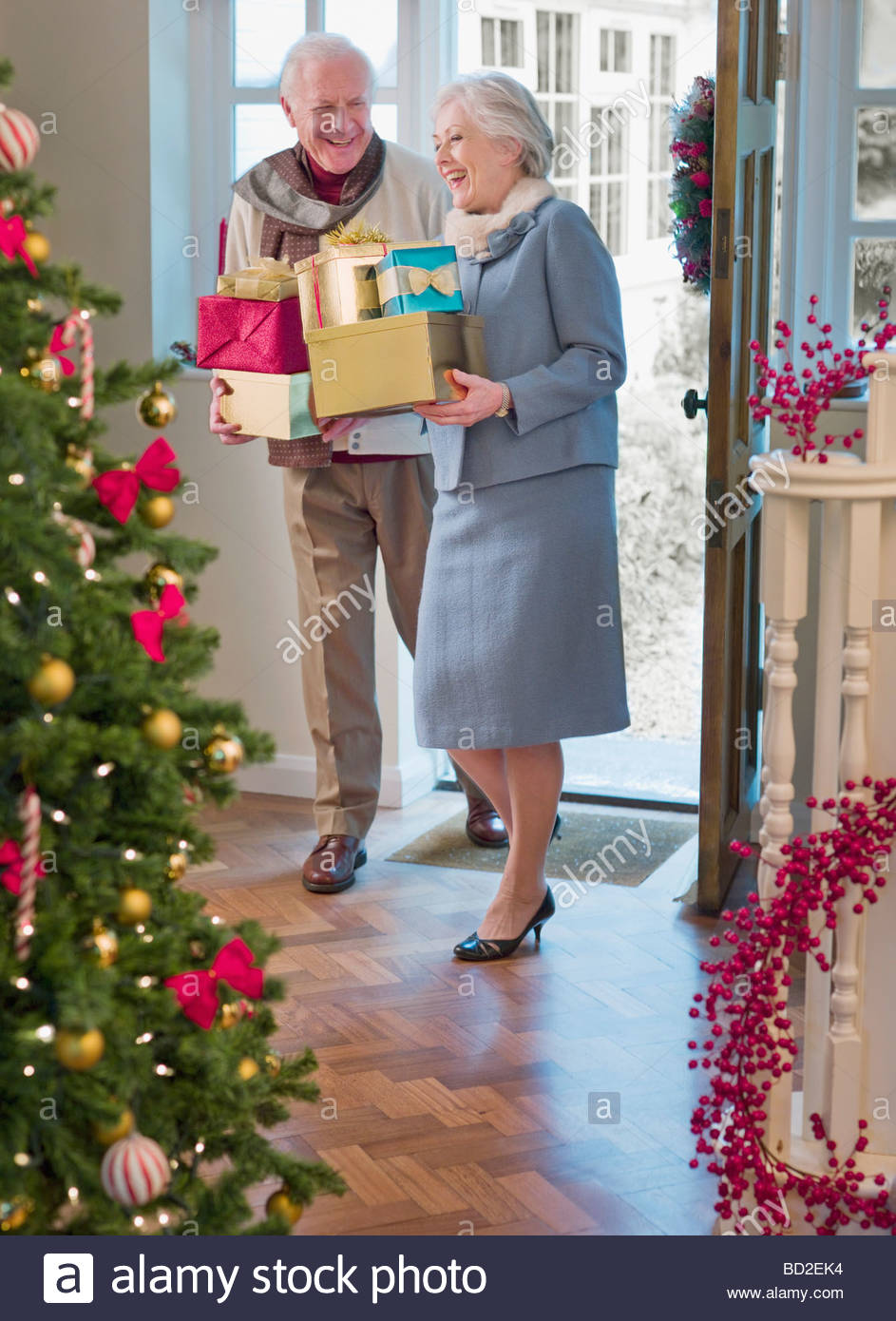 Couple entering house with Christmas gifts - Stock Image