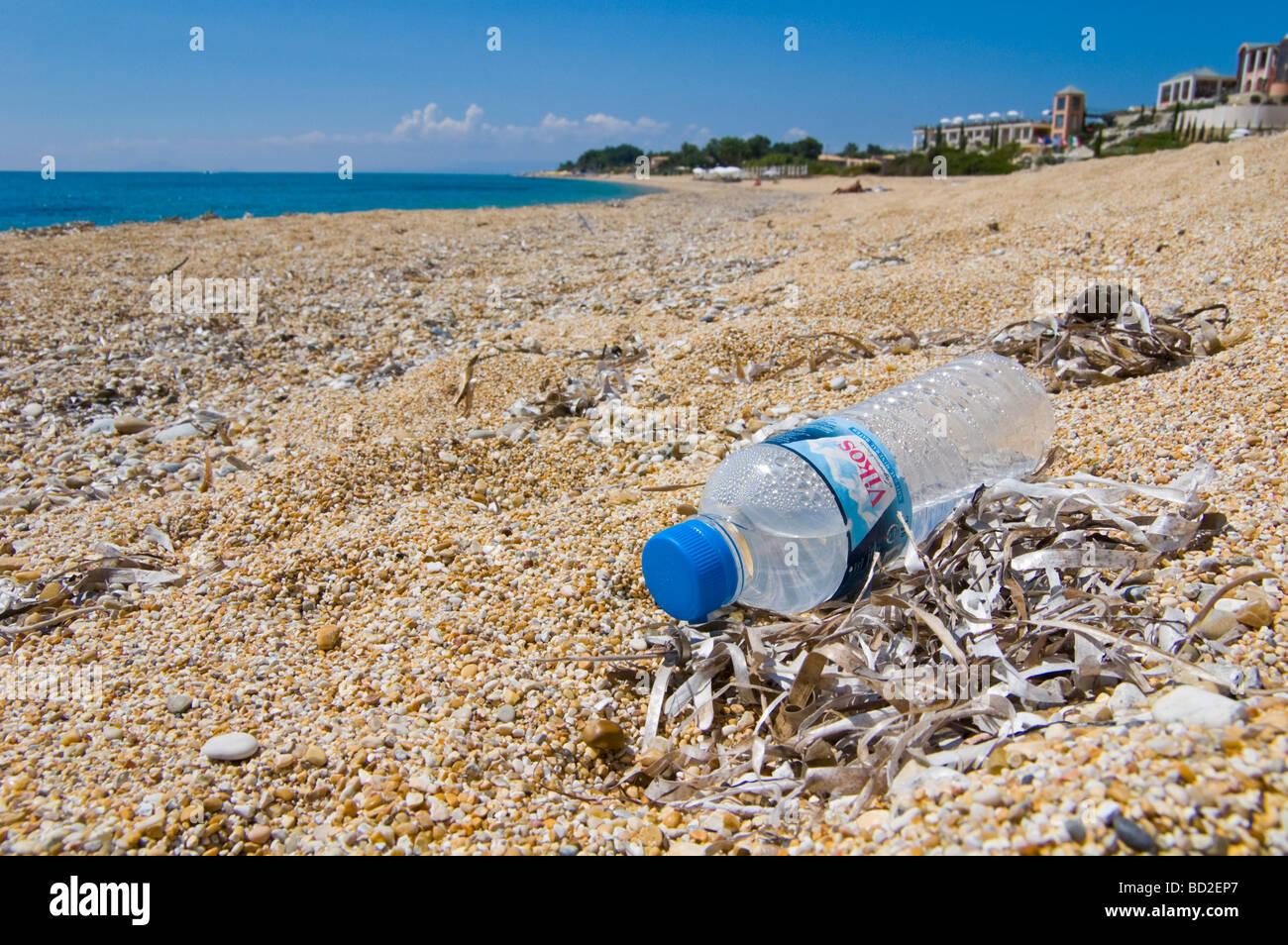 Plastic water bottle dropped as litter on beach at Skala on the Greek island of Kefalonia Greece GR - Stock Image