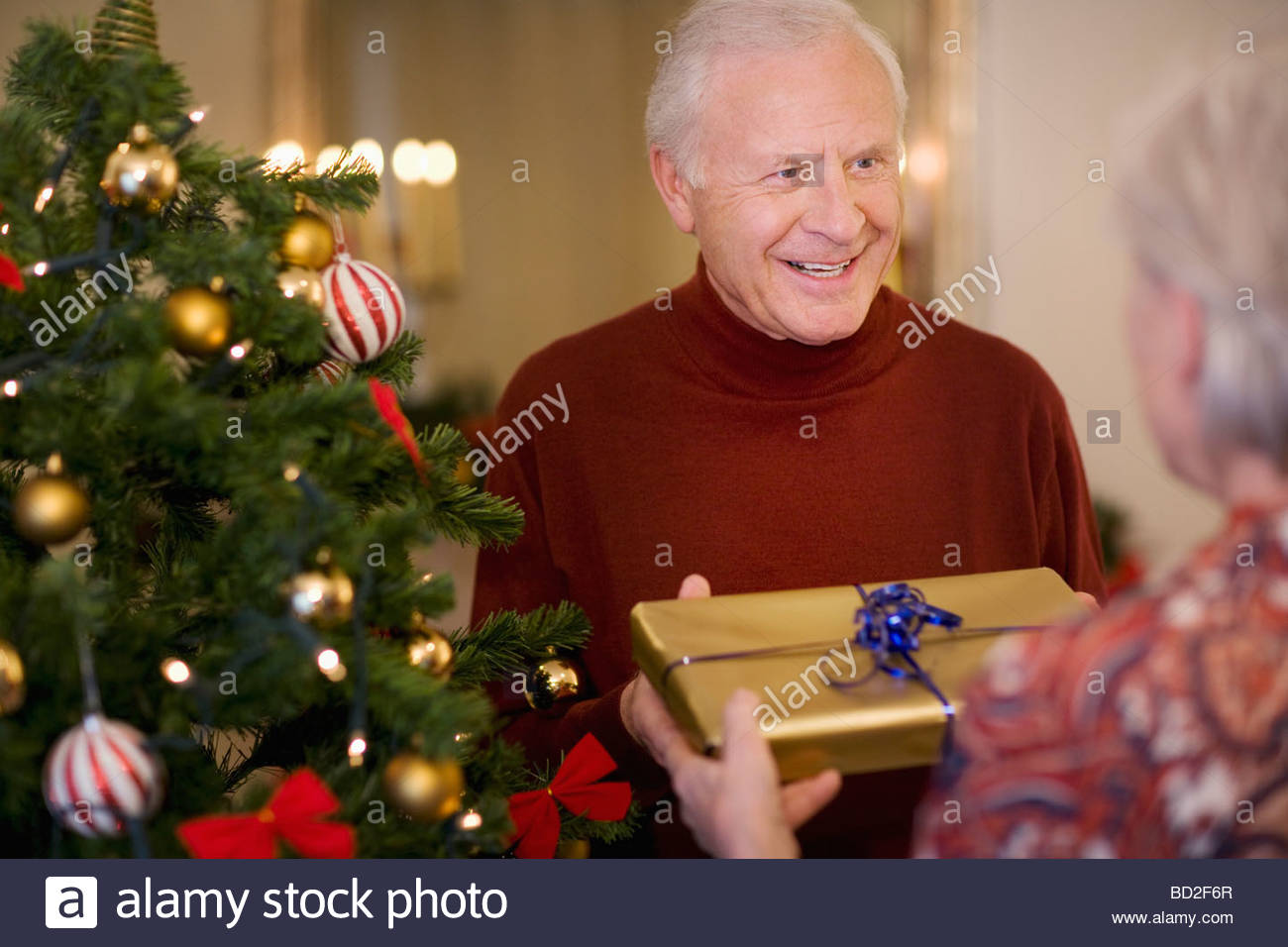 Couple with gift near Christmas tree Stock Photo