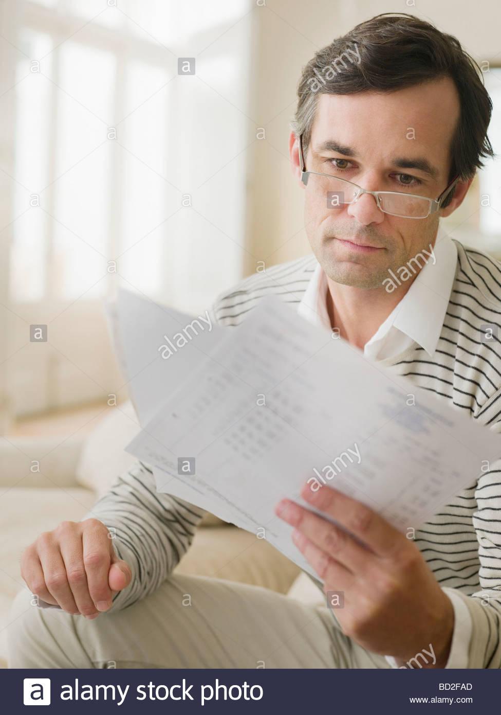 Man examining bills - Stock Image