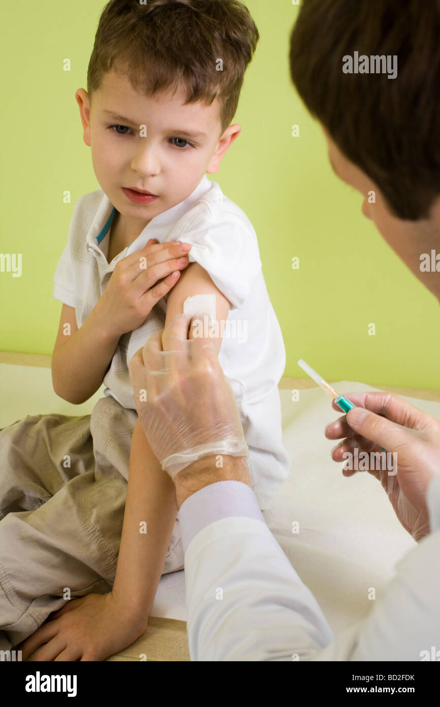 male doctor giving injection to a boy Stock Photo