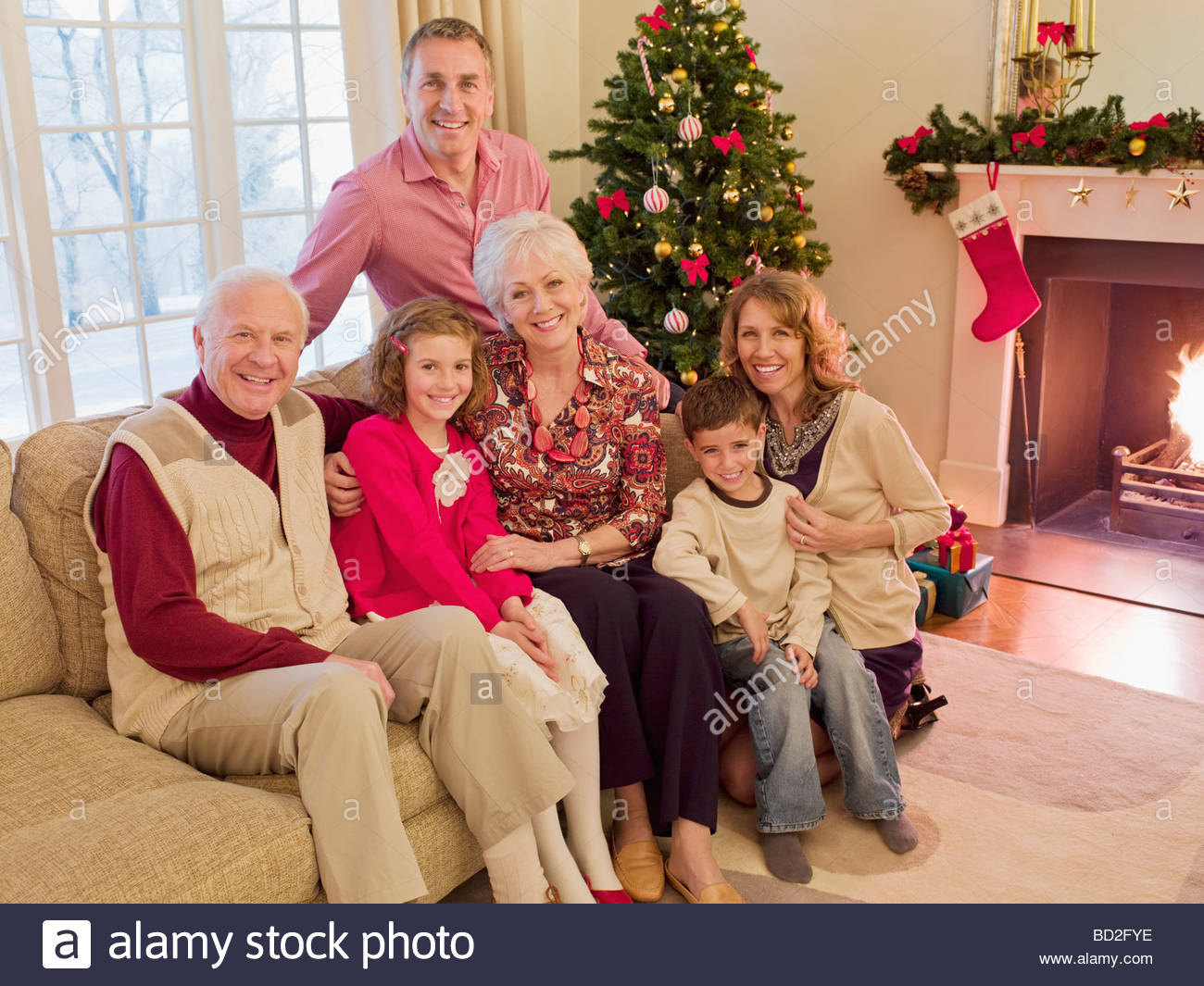 Multi-generation family near Christmas tree in living room Stock Photo