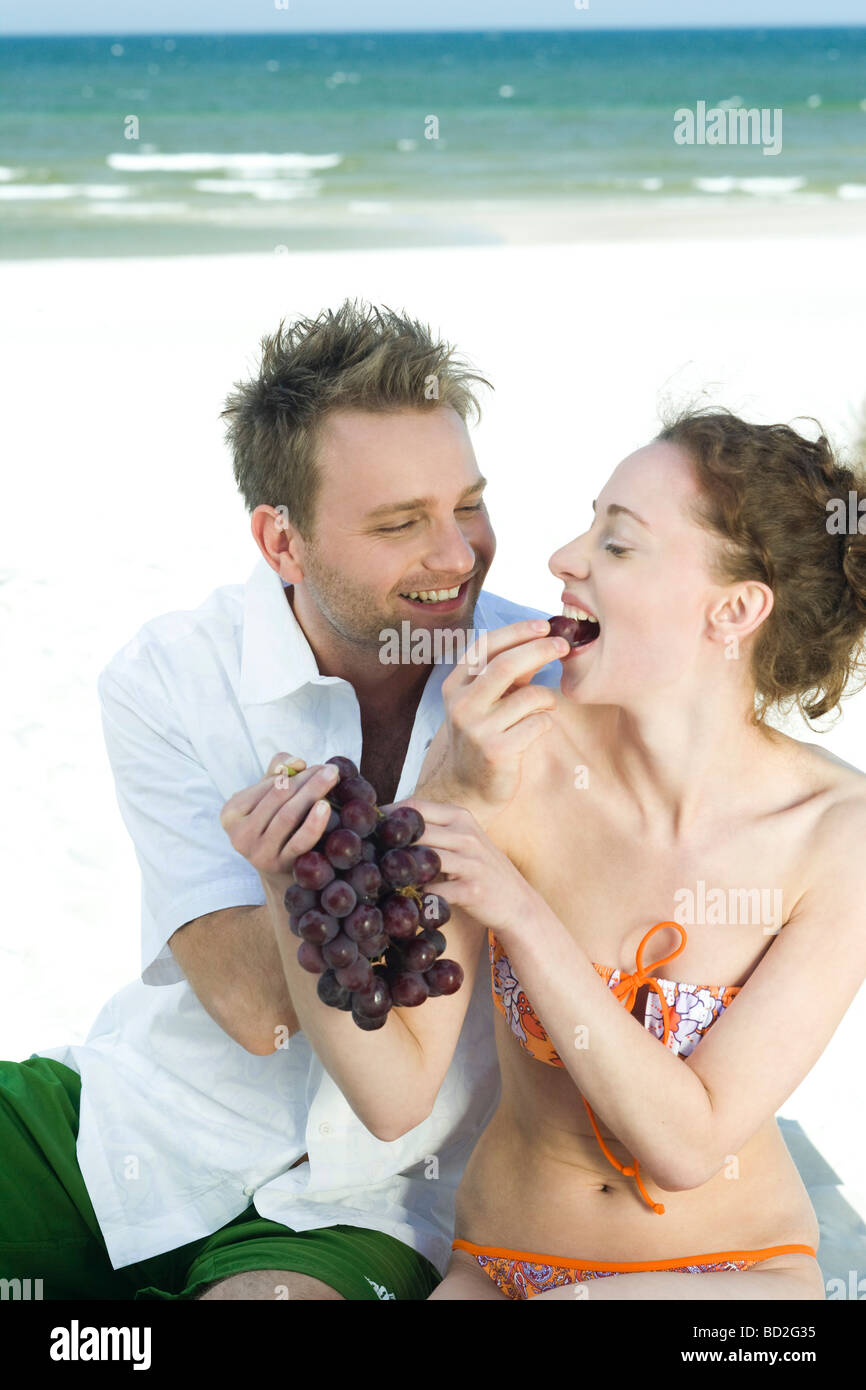 couple eating grapes on beach - Stock Image
