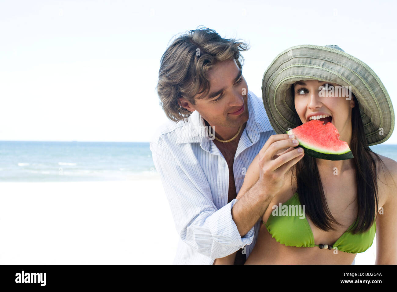 couple eating watermelon on beach - Stock Image