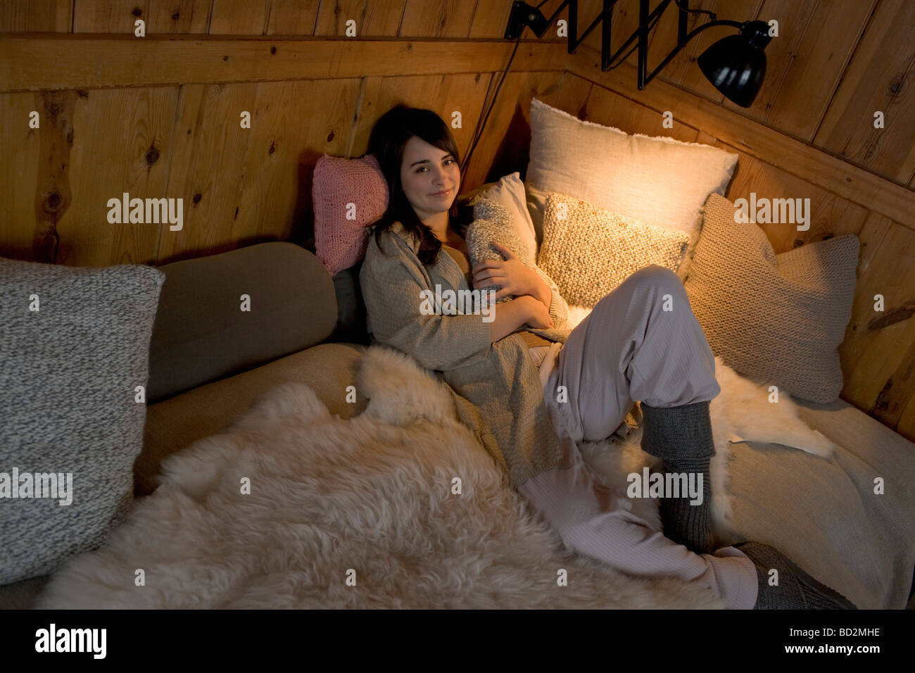 Young woman relaxing in bed - Stock Image