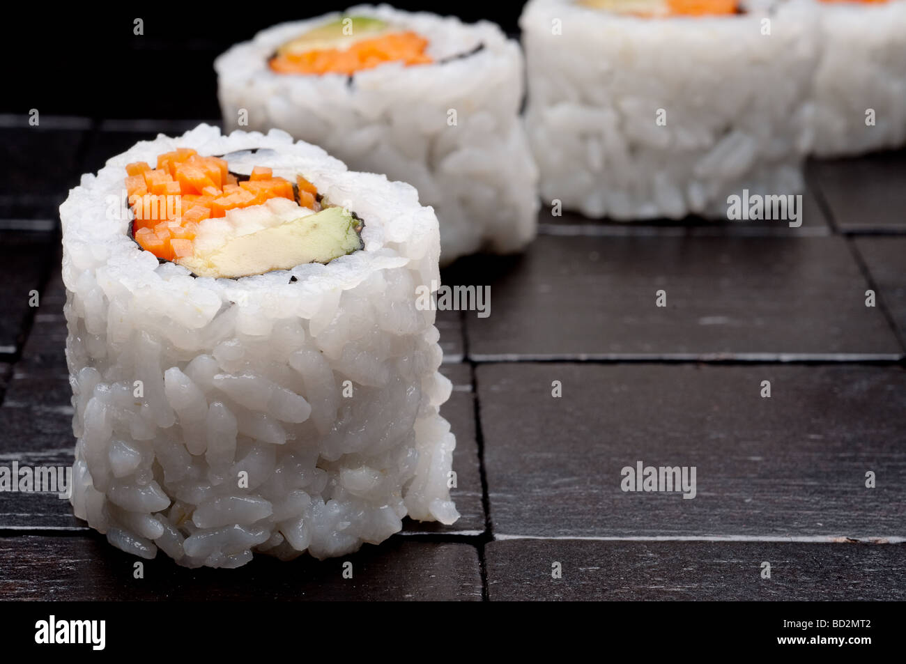 a horizontal shallow focus macro of sushi on a black wooden background - Stock Image
