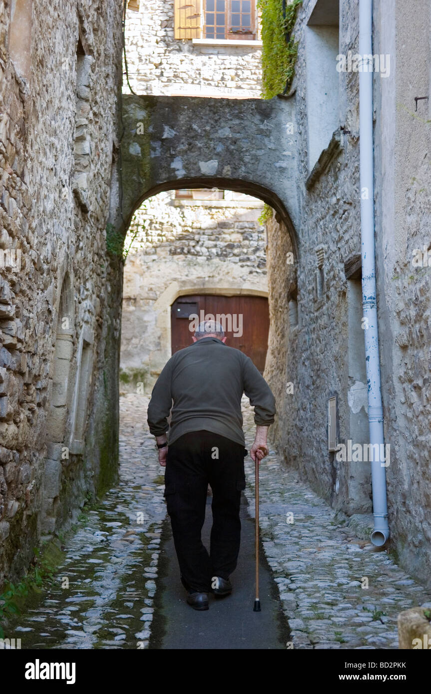 Rear view of an old Frenchman with a walking stick along a cobbled path in the village of Vaison la Romaine. Provence, - Stock Image