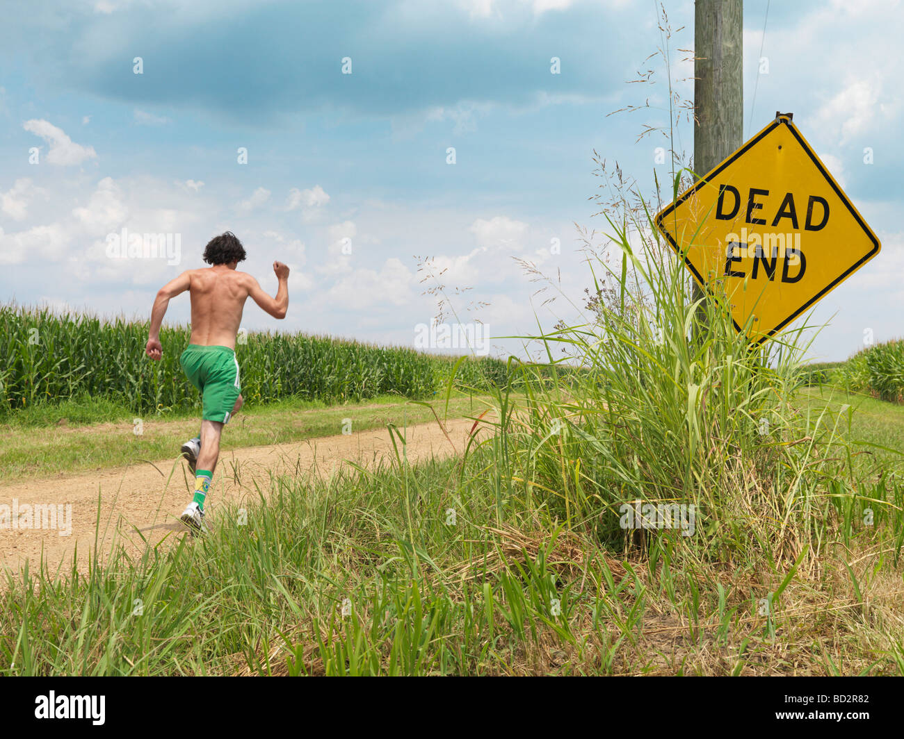 Man running along dirt road - Stock Image