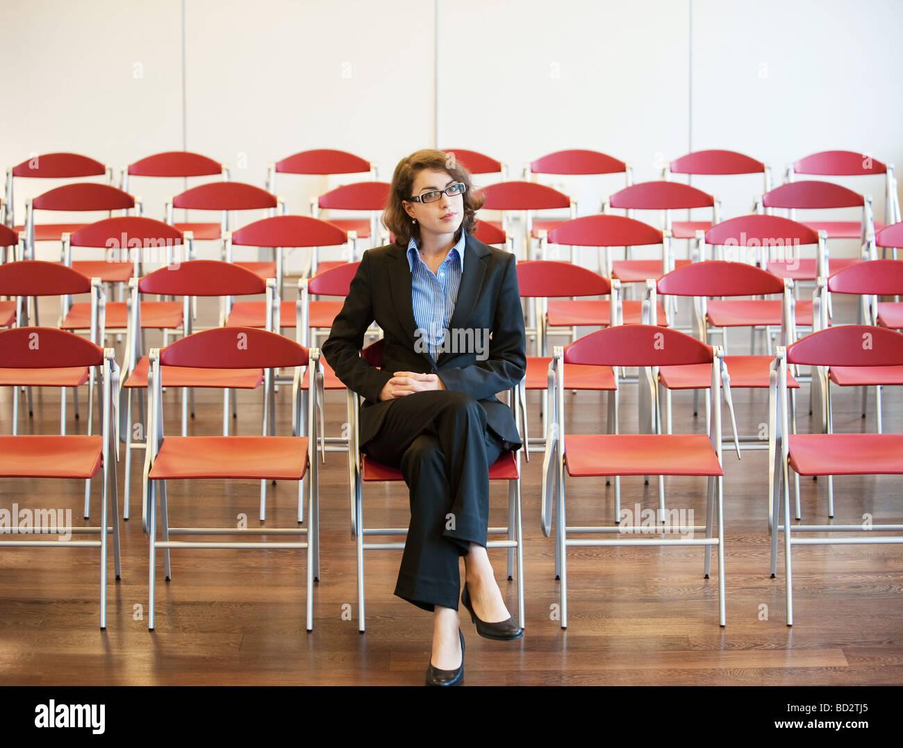 businesswoman among empty chairs - Stock Image
