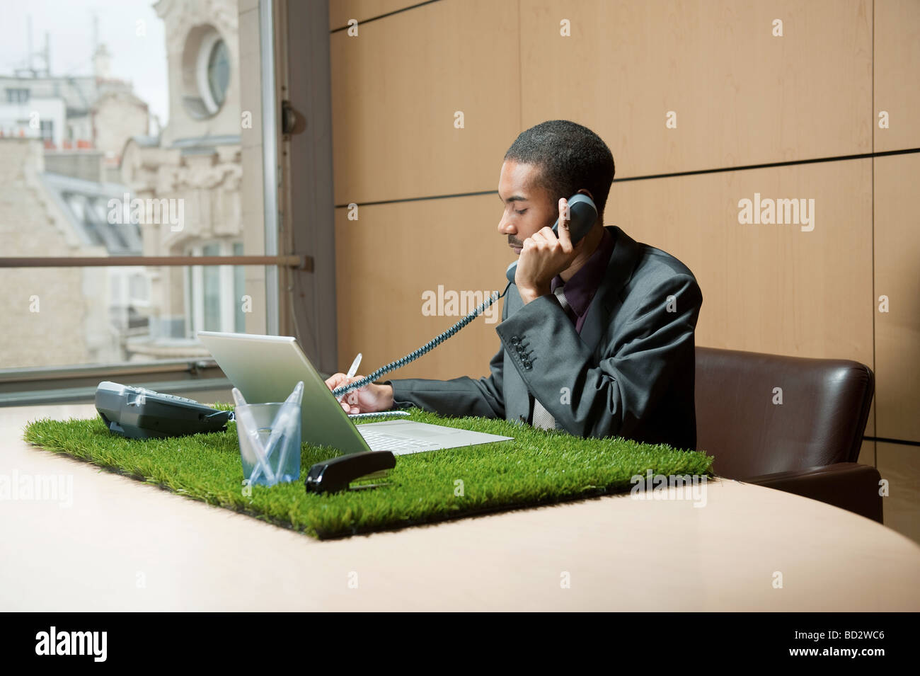 Man phoning at grass-covered desk - Stock Image