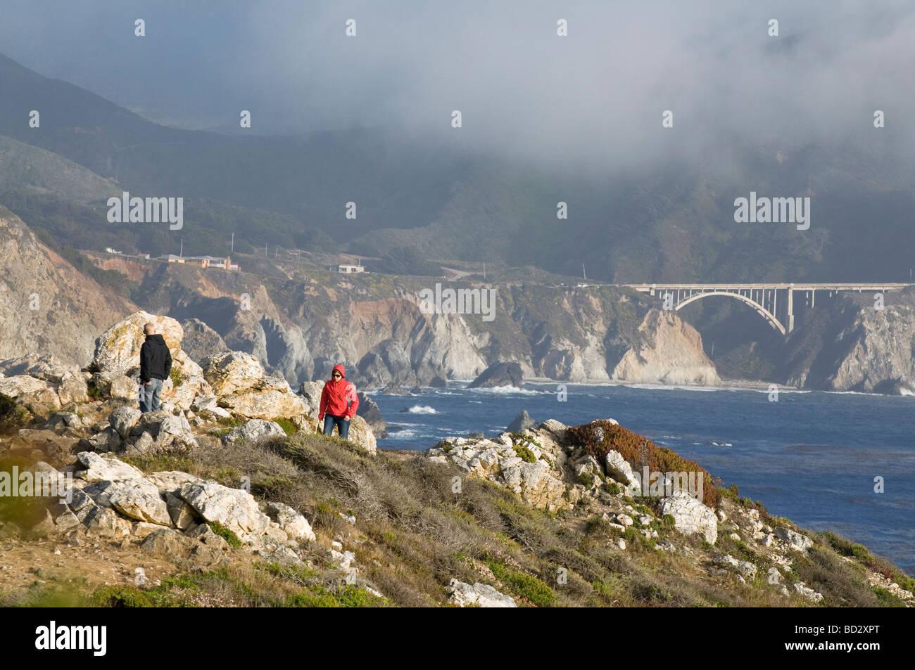 tourist hiking along the rocky coastal cliffs of Big Sur California - Stock Image
