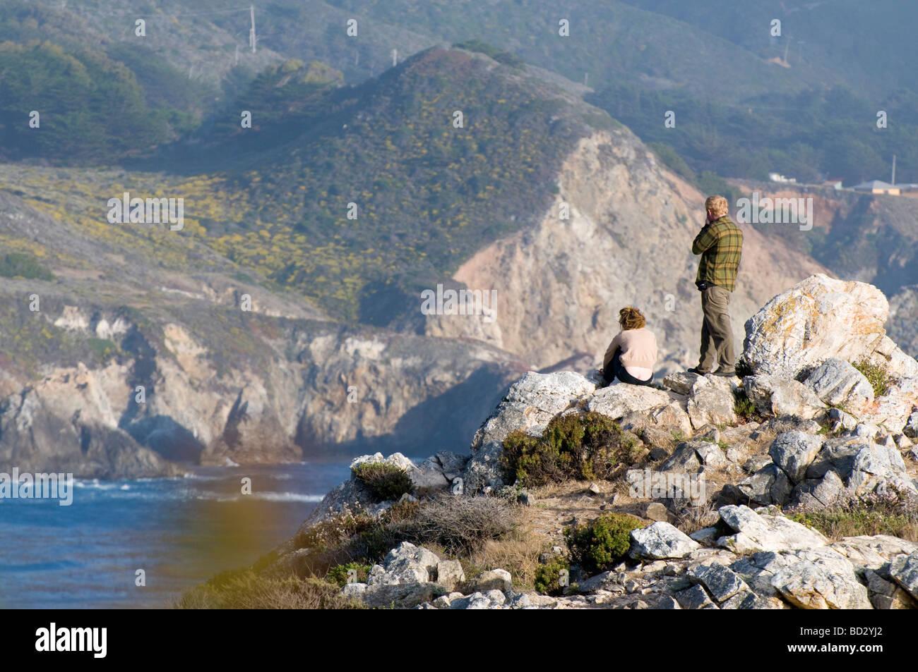 tourist overlooking the rocky coastal cliffs of Big Sur California - Stock Image