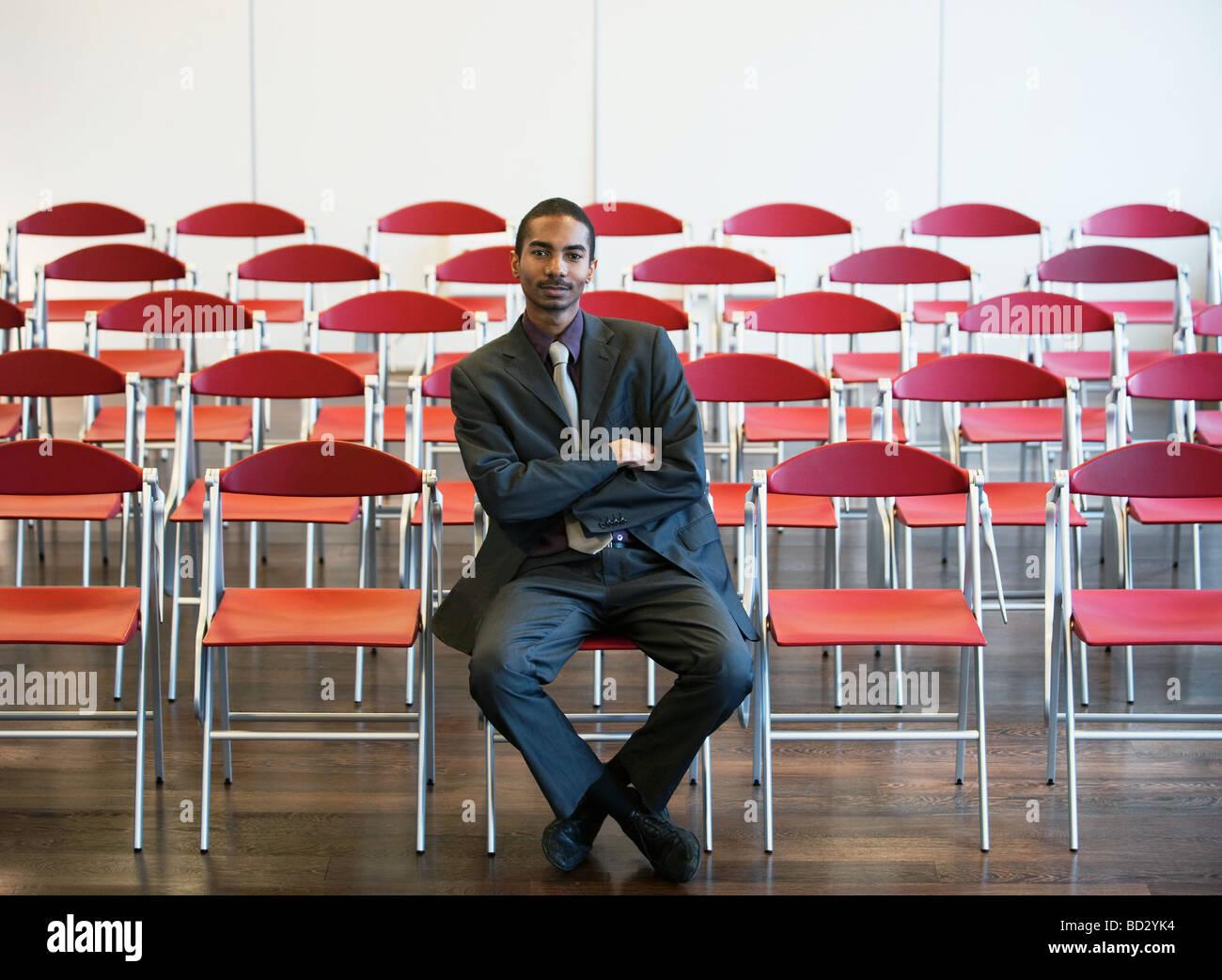 Black businessman among empty chairs - Stock Image
