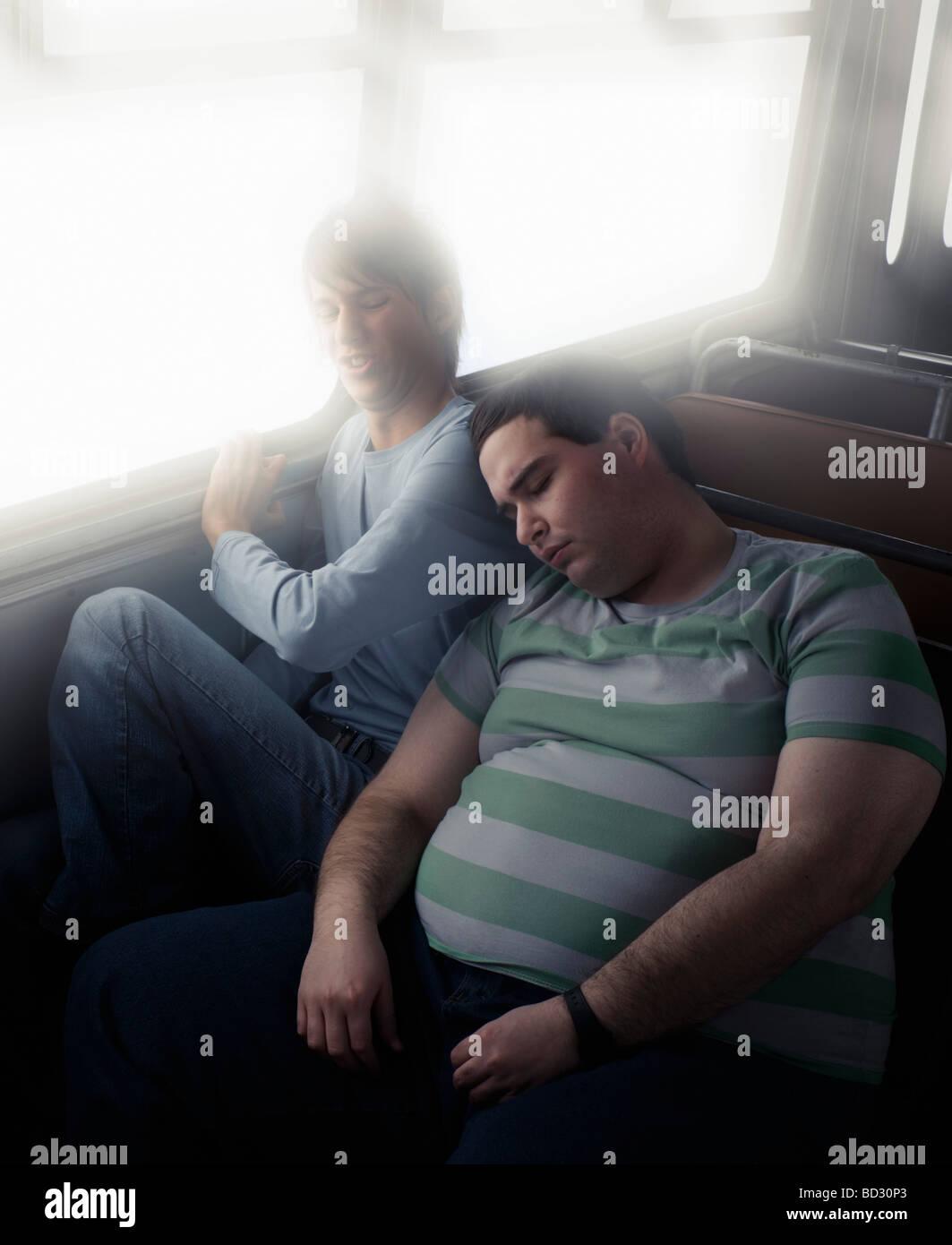 Thin boy squashed by fat boy - Stock Image