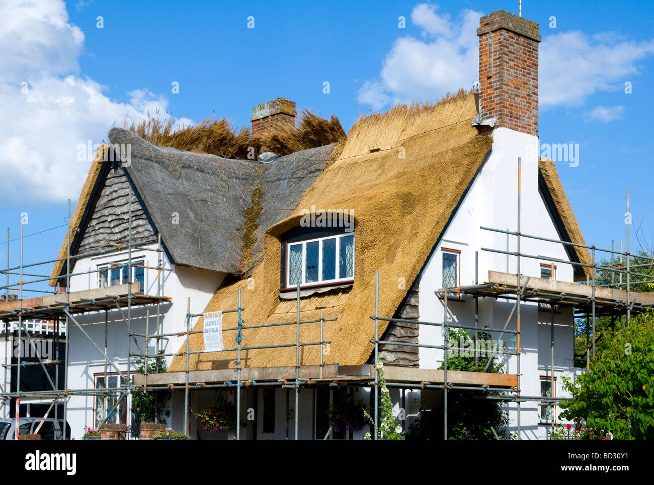 Old thatched roof in the process of being replaced by new thatch on a cottage in Walberswick, Suffolk, England. - Stock Image