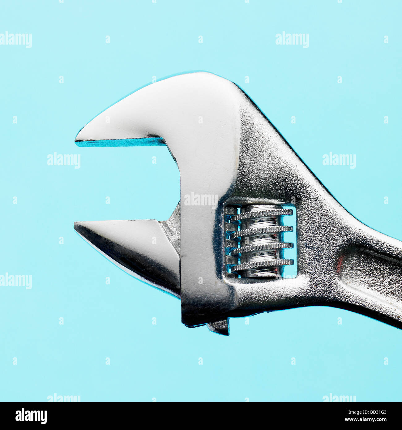 Adjustable chrome spanner on blue background. - Stock Image