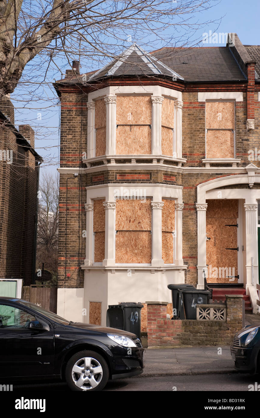 Boarded up semi-detached house in London - Stock Image