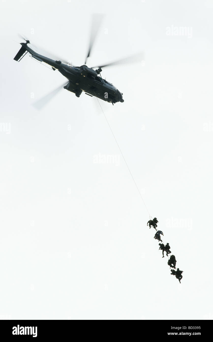 Soldiers descending from a helicopter on a rope, landing exercise of the airborne forces unit of the French military Stock Photo