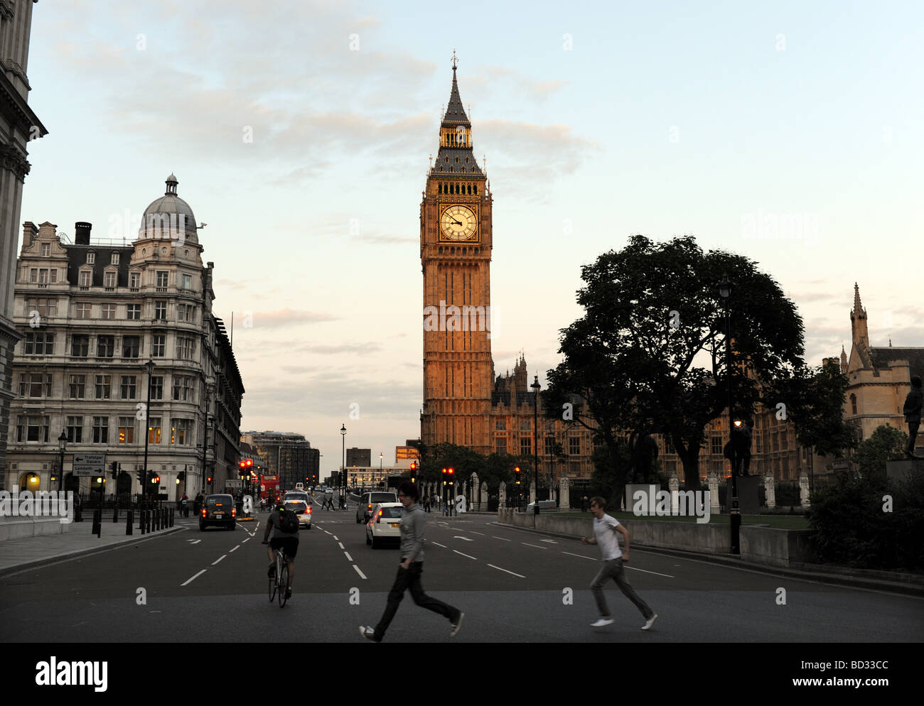 Pedestrians dash across the road by Big Ben in Parliament Square London at dusk - Stock Image