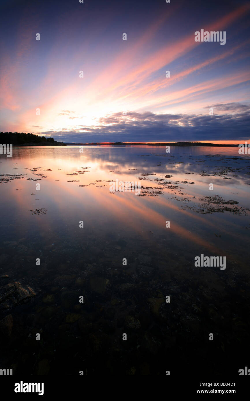Colorful skies and reflections at sunrise, at Teibern in Larkollen, Rygge kommune, Østfold fylke, Norway. - Stock Image