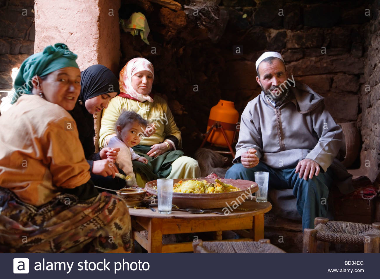 A Berber family eat a traditional tagine meal in a Moroccan house near Marrakech, Morocco Stock Photo