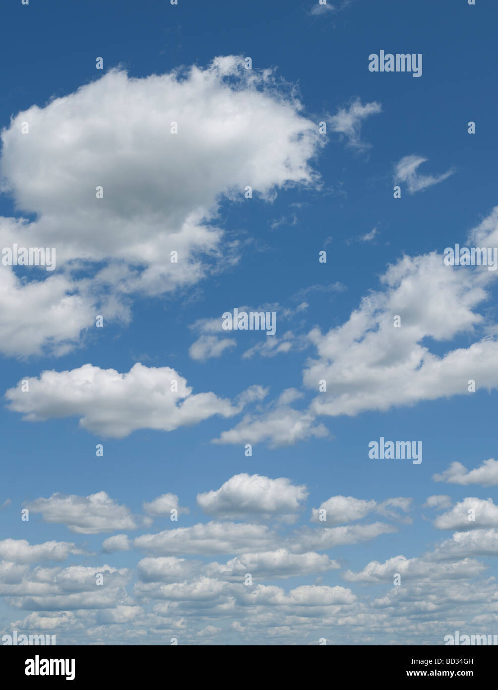 Blue sky puffy clouds - Stock Image