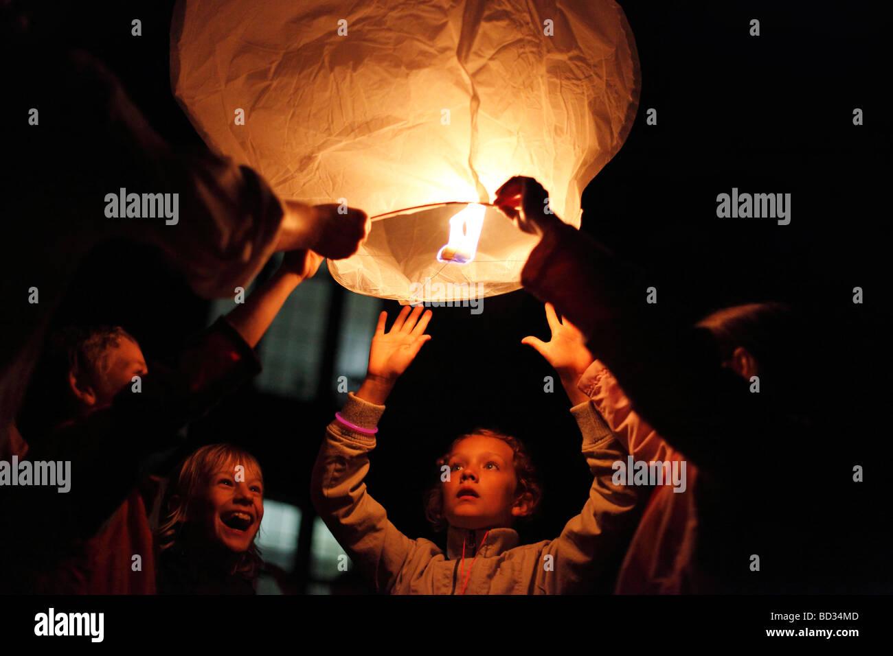 kids launch a sky lantern; floating lantern; Thai lantern; hot air balloon - Stock Image