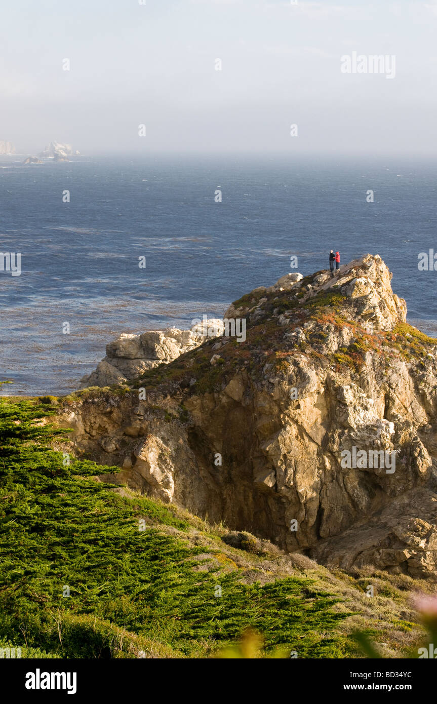 Tourists on rocky cliff overlooking the Pacific ocean Big Sur California - Stock Image