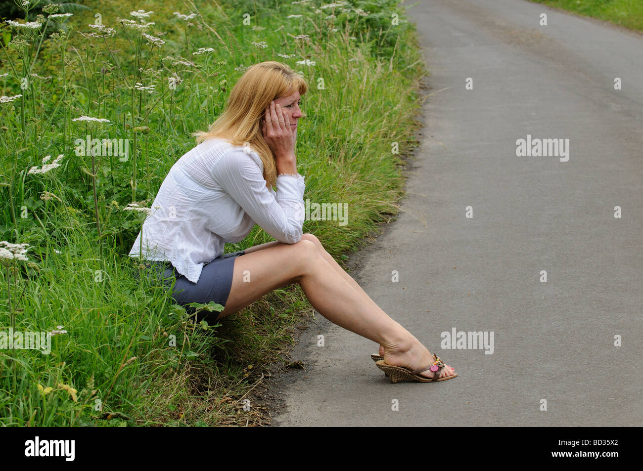 mature woman wearing a white shirt and skirt sitting on the roadside