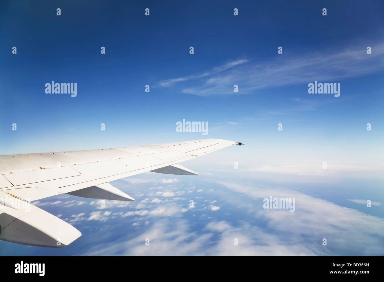 View from an aircraft window of an airplane wing and the Earth below - Stock Image