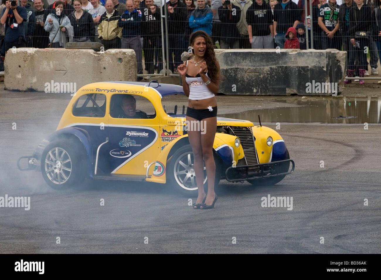 A stunt driver performing a stunt around a model at Santa Pod Raceway - Stock Image