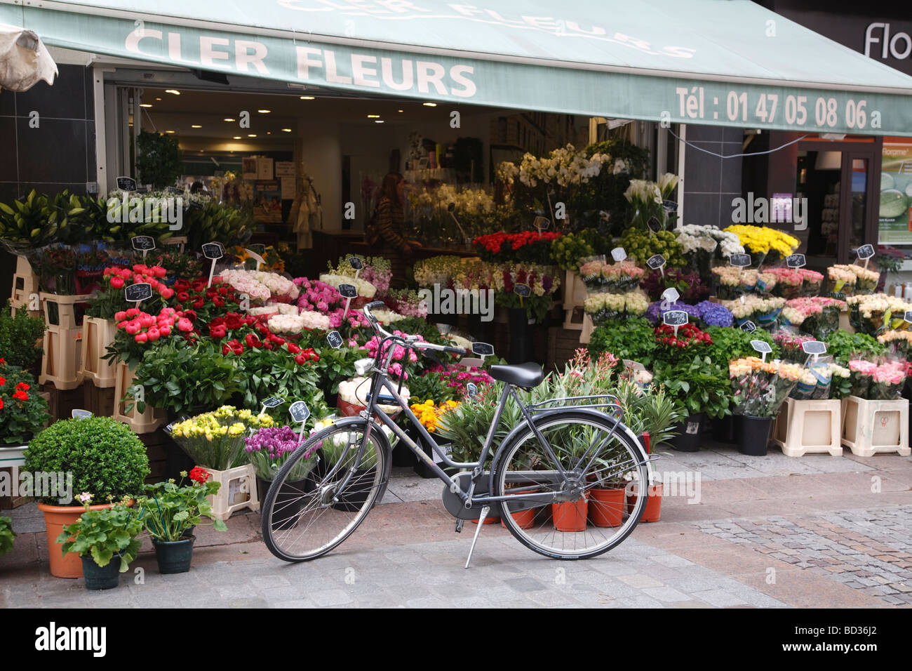 A traditional bicycle stands outside a flower stall on Rue Cler in Paris, France Stock Photo