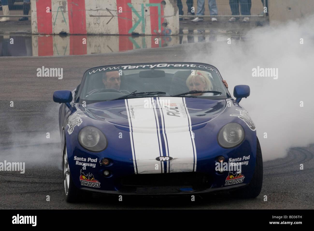 A stunt driver performing a stunt at Santa Pod Raceway - Stock Image