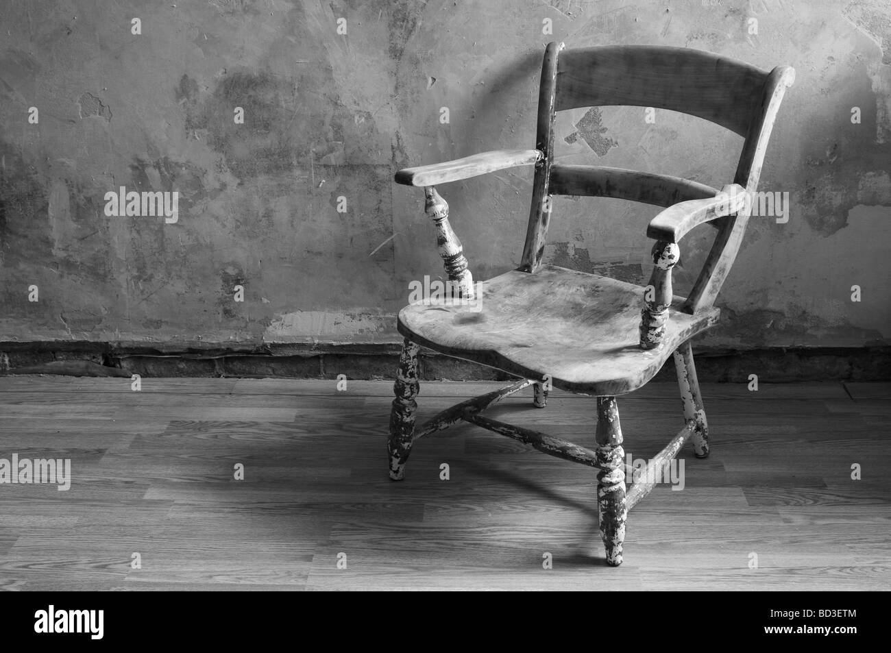 wooden chair on wooden floor, with bare plaster wall - Stock Image