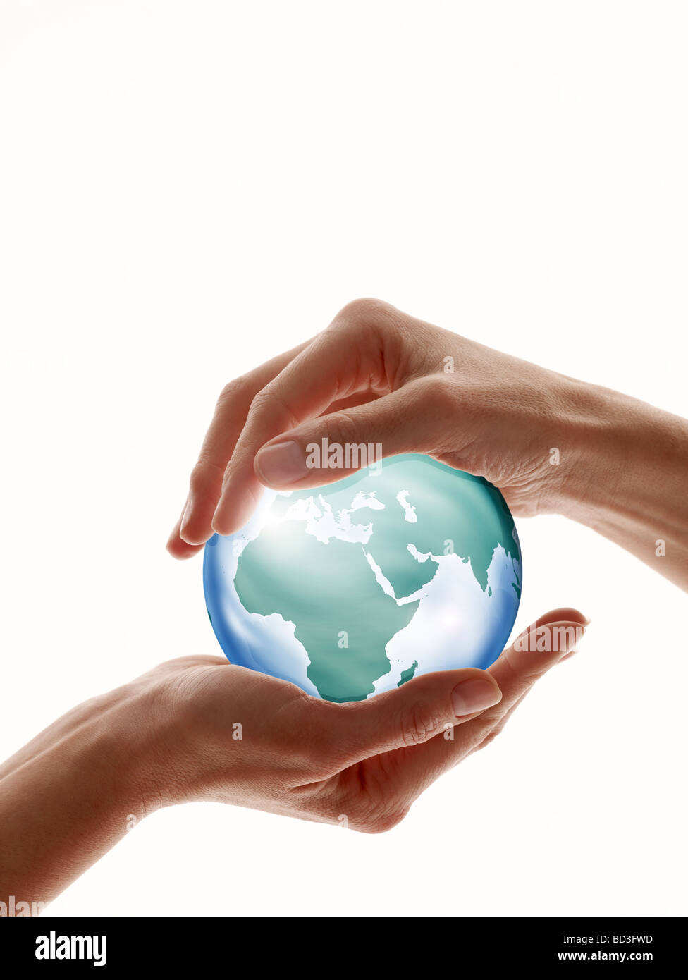 Two hands encircling glass globe isolated against white - Stock Image