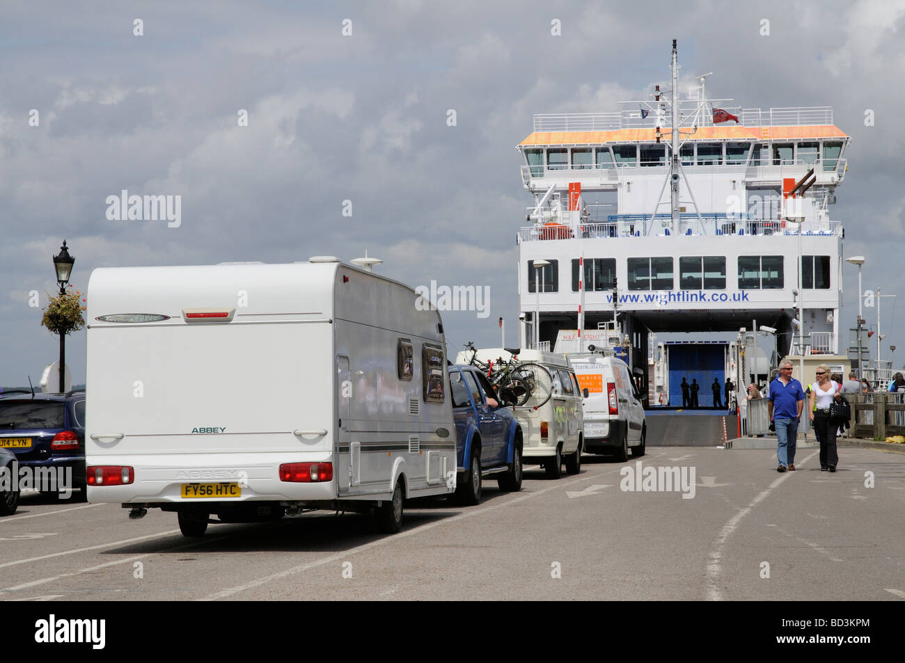 Vehicular traffic waiting to embark onto Wightlink Isle of Wight service ferry at Yarmouth southern England UK - Stock Image