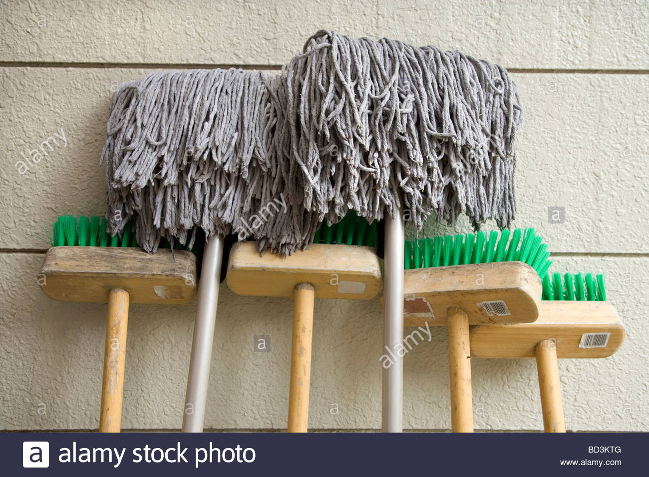 brooms and mops placed against a wall to dry - Stock Image