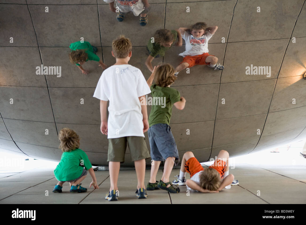 Tourists enjoy Anish Kapoor sculpture Cloud Gate aka the Bean in Millennium Park in Chicago Illinois - Stock Image