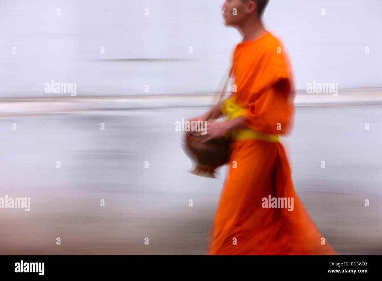 monks walking through the streets at dawn to collect gifts of food, Luang Prabang, Laos - Stock Image