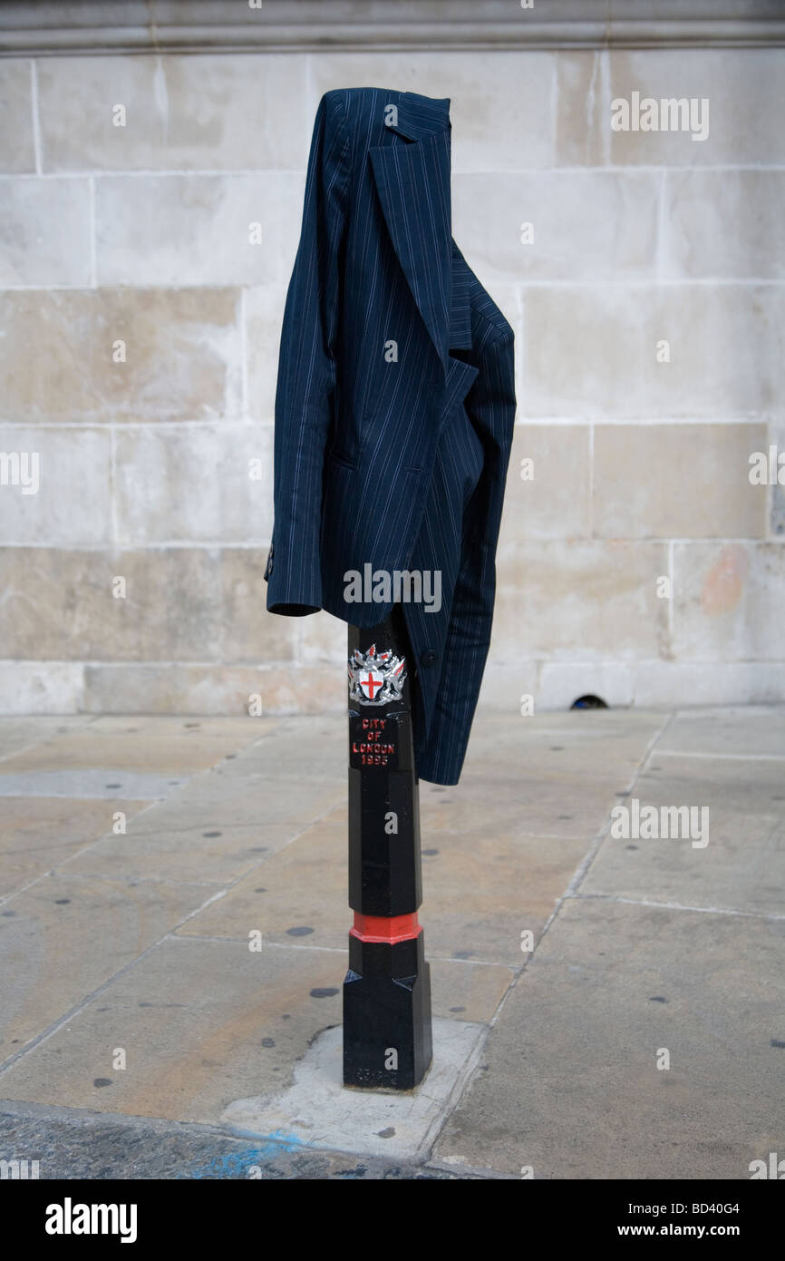 a man's jacket hanging over a bollard in the city of london - Stock Image
