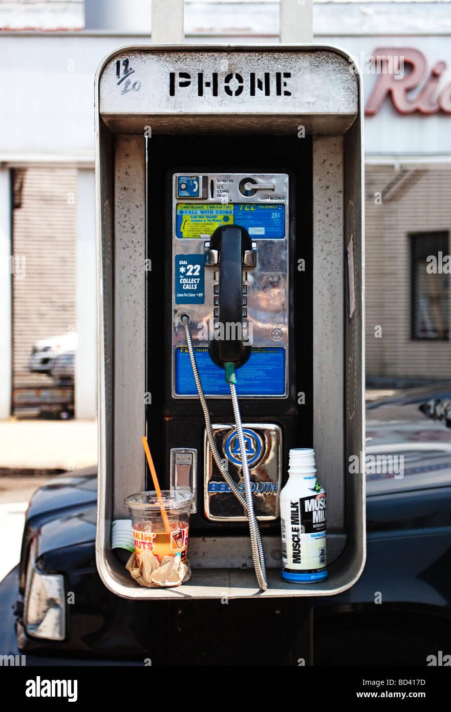 Phone box street with breakfast: coffee and milk. Public phone on Brooklyn street, New York City. - Stock Image