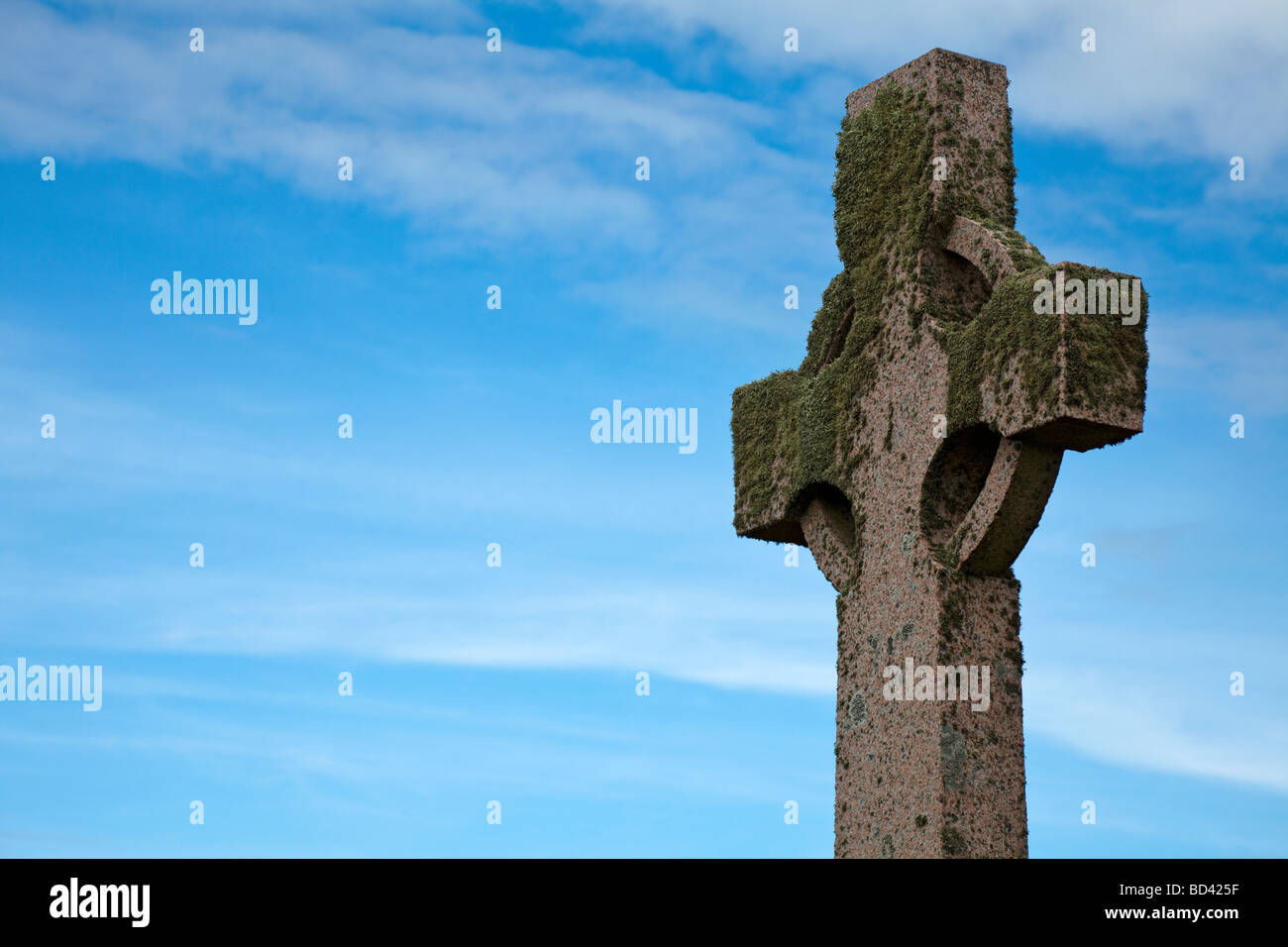 Weathered old Celtic Cross encrusted with moss and lichen photographed on Iona, a small Scottish island, in the - Stock Image