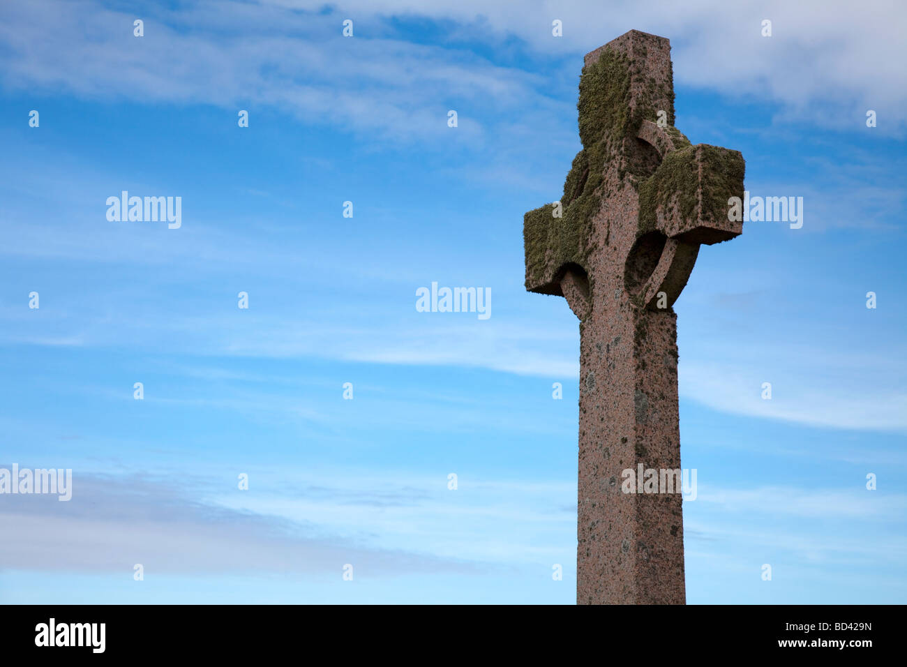 Celtic cross covered with moss and lichen, photographed on Iona, a small island in the Inner Hebrides group off - Stock Image