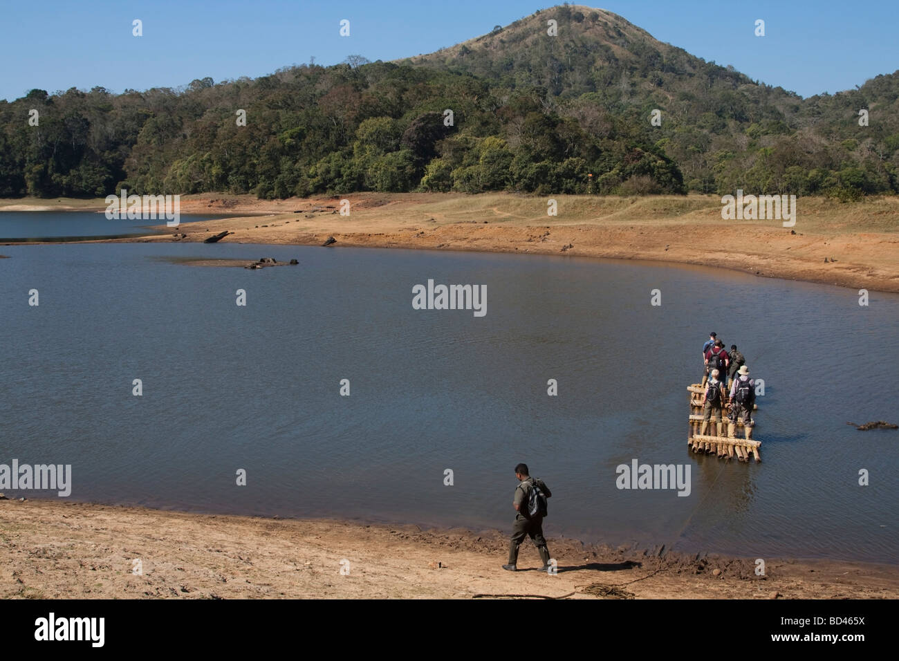 India Kerala Periyar national park tourist guide and eco tourists being ferried on bamboo raft - Stock Image