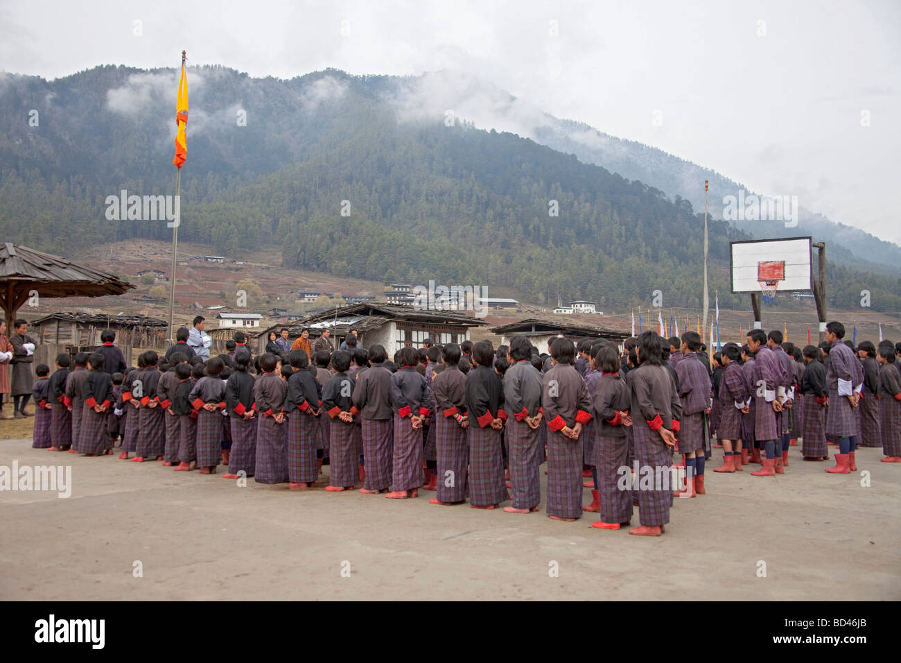 Group of young school children in red boots and uniforms at assembly in school playground 91957_Bhutan-Wangdue - Stock Image